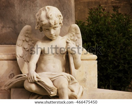 Beautiful angel child statue holding a lyre under his arm and a book on his knees. Location: Noto, Sicily. Carrara marble statue dated 1892.
