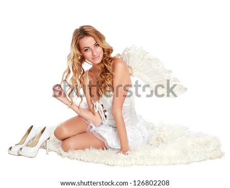 Beautiful angel girl sitting on a white carpet, isolated on white - stock photo