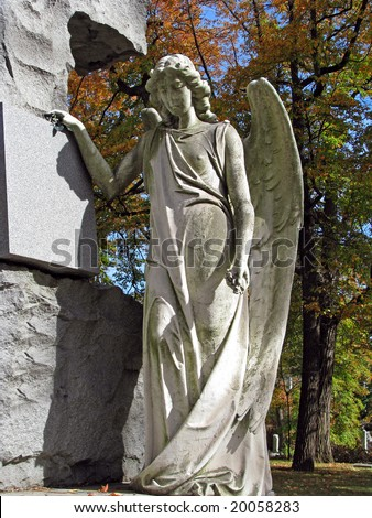 beautiful angel statue in colorful autumn cemetery - stock photo