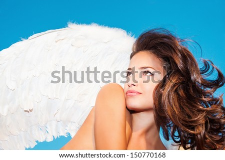 beautiful angel woman with white wings against blue sky small amount of grain added - stock photo
