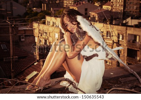 beautiful angel woman with white wings sit on roof edge holding cat, view of the city  in background