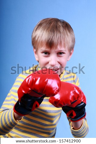 Beautiful angry blond boy boxing wearing red boxer gloves fighting and looking dangerous