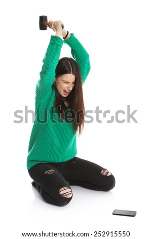 Beautiful angry lady with green sweater and black broken pants breaks mobile phone with hammer. Isolated on white. - stock photo