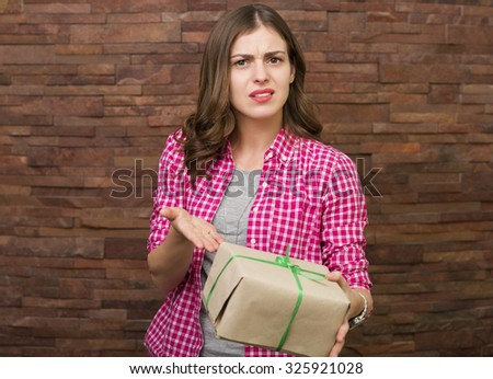 Beautiful annoyed woman opening a gift box - stock photo