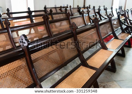 Beautiful, antique, church pews, exquisitely handcrafted from stained hardwood and wicker, arranged in their traditional rows and still in use for religious services. - stock photo
