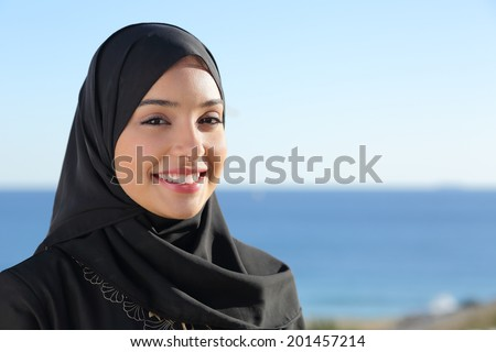Beautiful arab saudi woman face posing on the beach with the sea in the background                 - stock photo