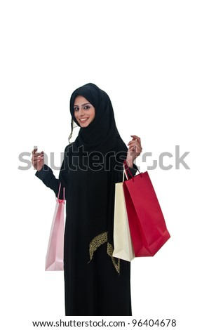 Beautiful arab traditional woman holding shopping bags - stock photo