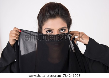 Beautiful Arab woman in traditional dress covering her face on white background