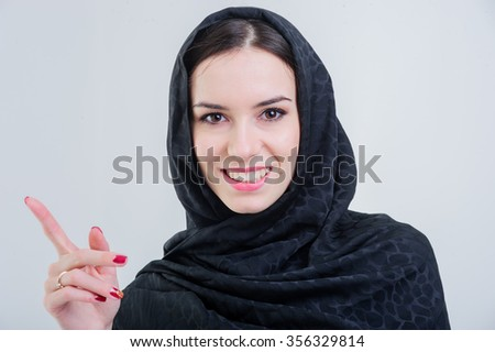 Beautiful arab woman with pointing finger isolated on grey background. - stock photo