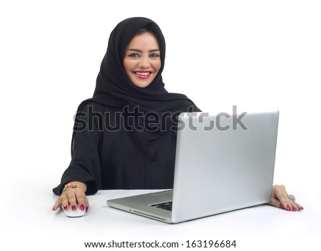 Beautiful Arabian business woman working on her laptop - stock photo