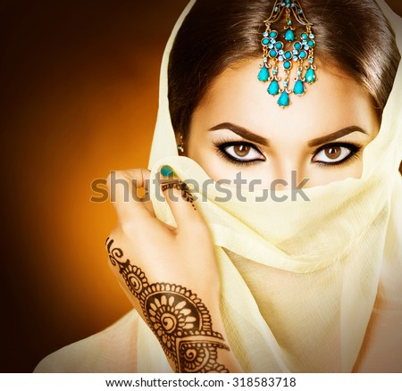 Beautiful Arabian girl portrait. Young Hindu woman with mehndi tattoos from black henna on her hands. Portrait of beauty Indian model with bright make-up who hiding her face behind the veil  - stock photo