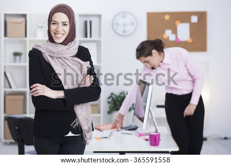 Beautiful Arabic business woman working in her office with her worker in blur. Two business women,Shallow depth of field - stock photo