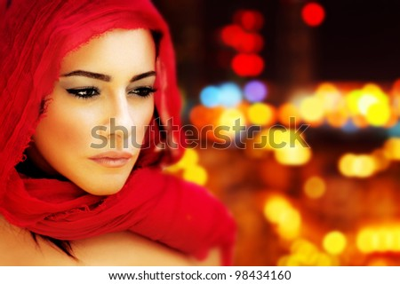 Beautiful Arabic woman wearing red scarf, stylish female face portrait over night city,  blur lights abstract  background, serious expression, stunning sensual beauty, model on the street - stock photo