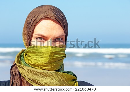 Beautiful arabic woman with green scarf at the ocean - stock photo