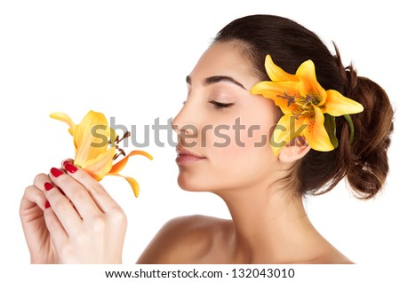 Beautiful Arabic woman with yellow lily flower in head enjoying flower scent, brunette girl with closed eyes isolated on white background, relaxation in day spa, aroma therapy - stock photo