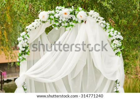Beautiful arch for the wedding ceremony, decorated with a white cloth and flowers, summer