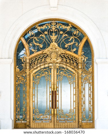 Beautiful arched doorway. Door made of wood, gold and glass reflecting arch. White wall of building with elegant gilded entrance. Old style of door with golden ornate details. Tourist attraction. - stock photo