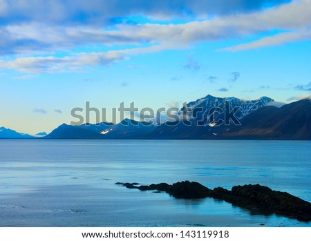 Beautiful arctic landscape with calm blue water of Greenland Sea and distant mountain range against the background of dramatic cloudy sky in Spitsbergen (Svalbard island) Norway - stock photo