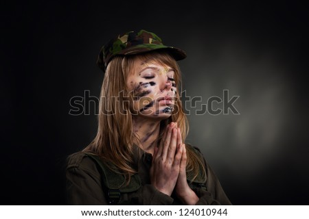 Beautiful army girl pray closed eyes clasp hands palms, soldier woman in a military uniform over black background