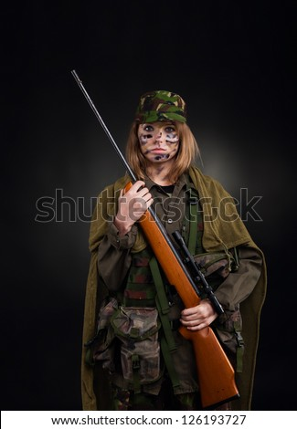 Beautiful army girl, soldier woman with rifle military uniform over black background