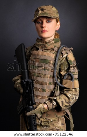 Beautiful army girl with rifle isolated on black - stock photo