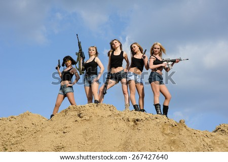 Beautiful army girls with guns  outdoors - stock photo