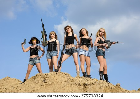Beautiful army girls with guns  outdoors