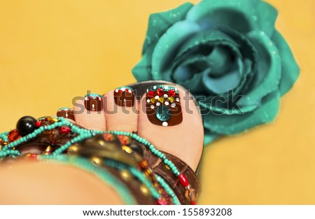 Beautiful art nail design women's feet in sandals with a rose on a yellow background. - stock photo