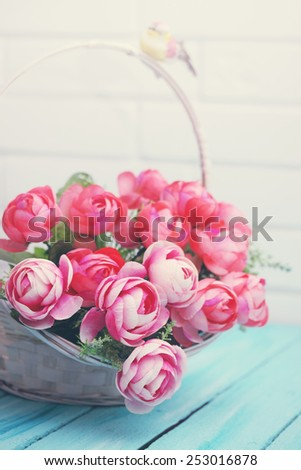 Beautiful artificial roses in a wicker basket - stock photo