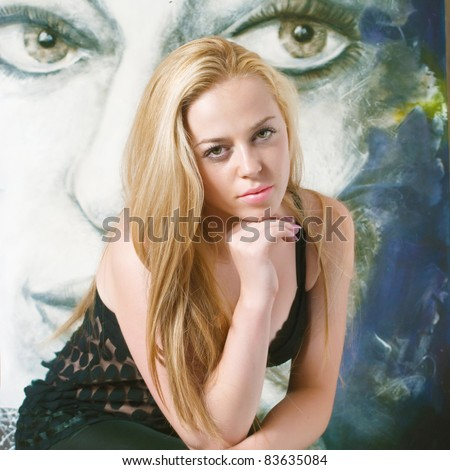 beautiful artist in the studio in front of her picture - stock photo