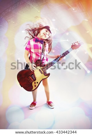 Beautiful artistic little girl playing guitar on blurred illumination background - stock photo