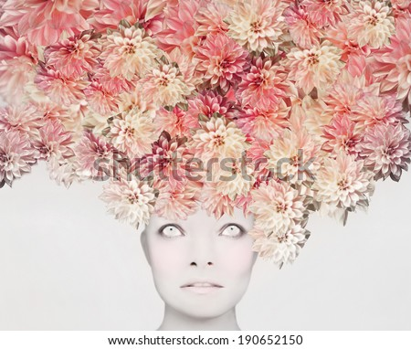 Beautiful artistic portrait of a young woman with an extravagant colorful floral headdress  - stock photo