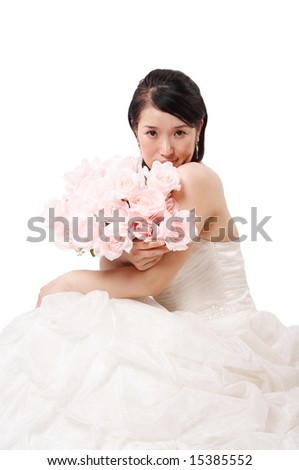 Beautiful asian bride holding a bundle of pink roses, isolated on white.