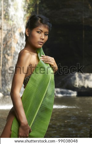 Beautiful Asian brunette model wearing bikini standing in front of scenic jungle waterfall in Thailand forest on sunny day covering herself with large leaf from banana tree.