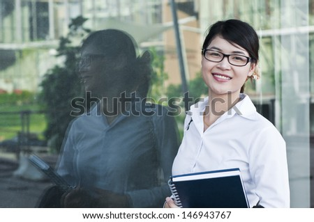 Beautiful Asian business woman and her reflection in glasses.