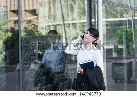 Beautiful Asian business woman and her reflection in glasses. - stock photo