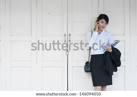 Beautiful Asian business woman calling with mobile phone.