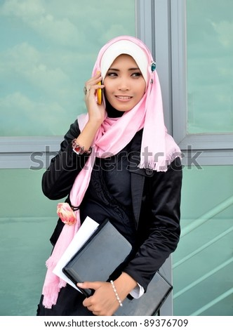 Beautiful asian business woman talking on cell phone with laptop - stock photo