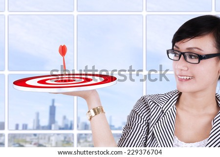 Beautiful asian businesswoman holding a target at modern office - stock photo