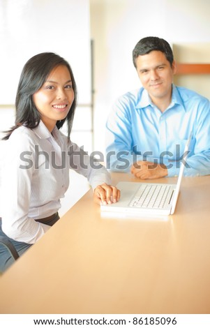 Beautiful Asian businesswoman leader sitting at laptop in conference room table meeting with handsome Hispanic businessman, cheerful, smiling, looking at camera in high-key office. Vertical