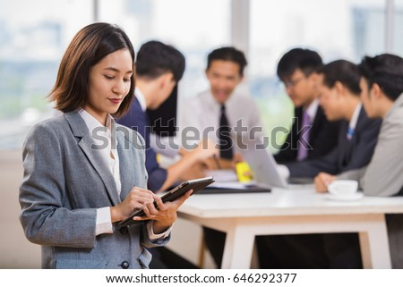 Beautiful Asian businesswoman smiling with confidence holding a tablet. Have a blurred Entrepreneurs and business people conference in modern meeting room.
