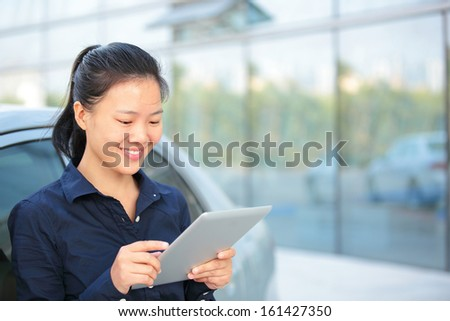 beautiful asian businesswoman use digital tablet leaning on car outside of modern office building