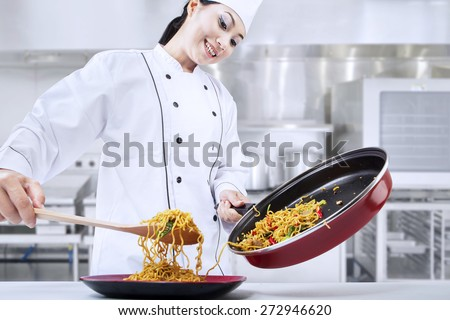 Beautiful asian chef cooks fried noodle in the kitchen - stock photo