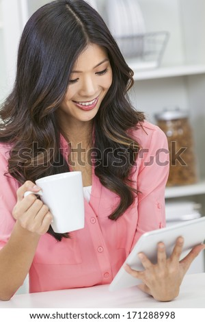 Beautiful Asian Chinese Woman Using Tablet Computer and drinking tea or coffee at home in her kitchen - stock photo