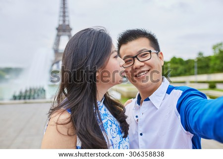 Beautiful Asian couple of tourists spending their vacation in Paris and taking selfie with a mobile phone with the Eiffel tower in the background - stock photo