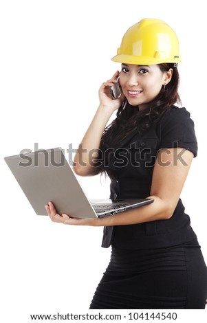 Beautiful Asian engineer holding laptop and a mobile phone - stock photo