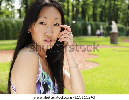 Beautiful Asian fashion model posing in blue dress. Outdors. Summer park.