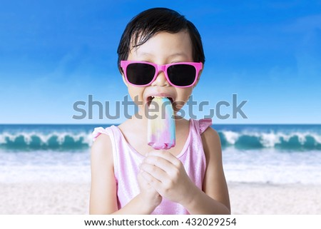 Beautiful asian female child wearing swimsuit and sunglasses on the beach while eating ice cream - stock photo