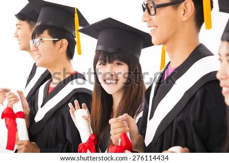 beautiful asian female college graduate at graduation with classmates - stock photo