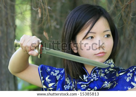 Beautiful Asian female in tradiional clothing with a sword
